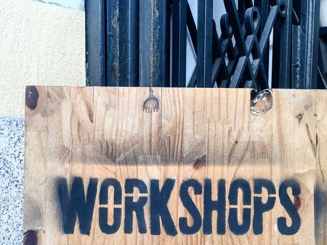 Wooden sign with Workshops painted on it with stencils